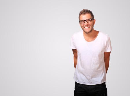 안경을 쓰고 웃고있는 흰색 티셔츠를 입고 젊은 남자 스톡 콘텐츠