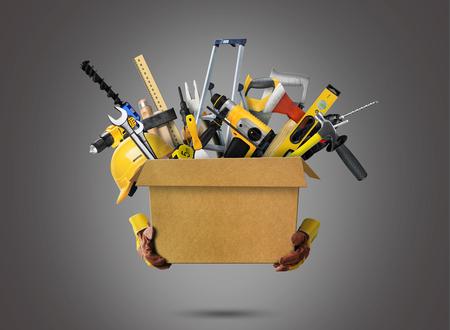 Construction tools and helmet in cardboard box Stockfoto
