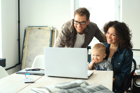 Young happy family relaxing at home at the table Stock Photo