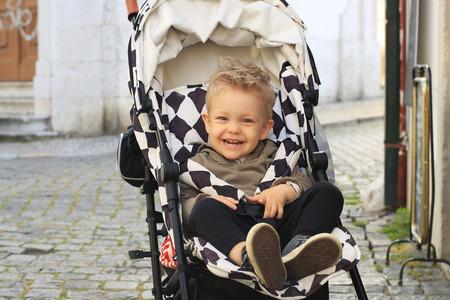 Little beautiful boy in a stroller on the street
