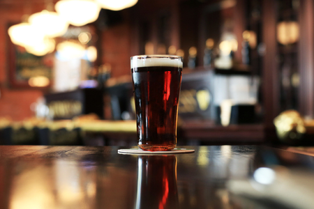 Glass of cold dark beer on the background of the bar