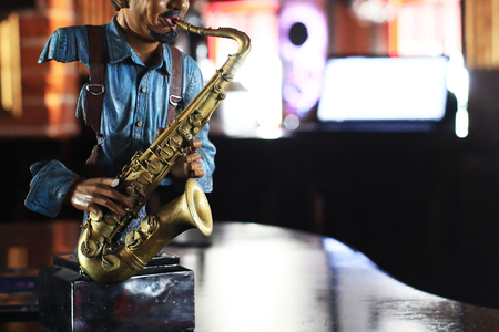 Figure of a musician with a saxophone on the background of the bar