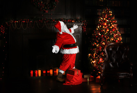 Christmas night, Santa Claus puts gifts under the tree Stock Photo