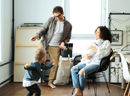 Happy young family laughing and dancing at home