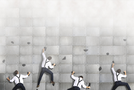 Business concept, a group of employees climbs up on the concrete wall
