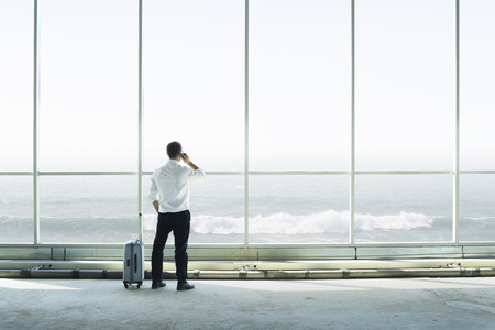 Businessman talking to a phone against a large window Stock Photo - 122697499