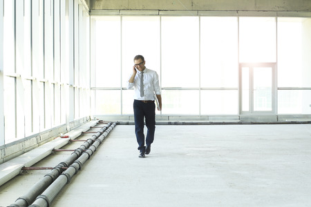 Young businessman talking on the phone in the big hall