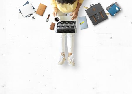 Young woman sitting and working on floor with book and laptop, business concept Zdjęcie Seryjne - 131718258