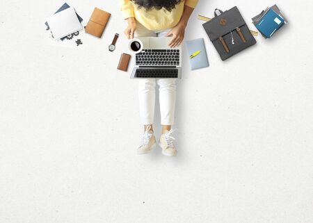 Young woman sitting and working on floor with book and laptop, business concept
