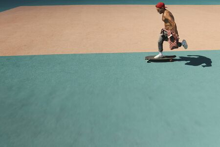 A young man rides a skateboard in a skate park
