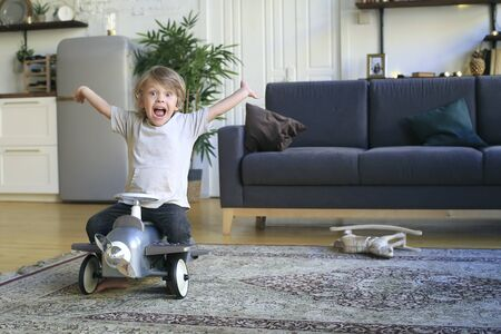 Little boy sits on the airplane and plays on the floor Stock Photo