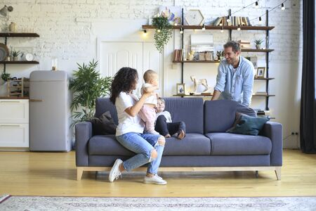 Young beautiful happy family relaxing at home
