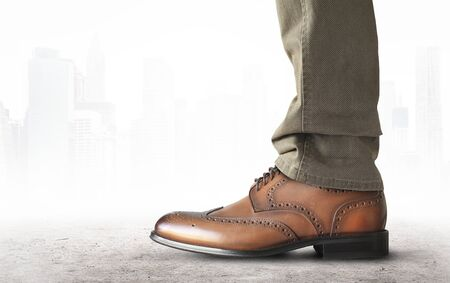 A man stands in brown classic leather mens shoes