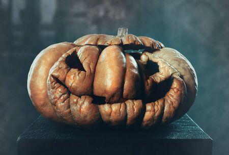 Scary old Halloween pumpkin on dark background Foto de archivo