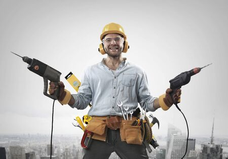 Construction worker with a hammer and drill at work Standard-Bild