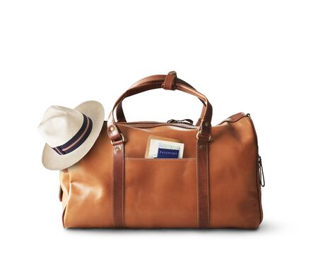 Vacation concept, large classic brown leather travel bag with hat Stock fotó