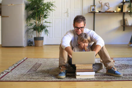 Young father freelancer working on the laptop at home Standard-Bild