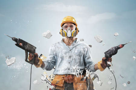 Construction worker in dirty clothes with a hammer and drill at work Standard-Bild