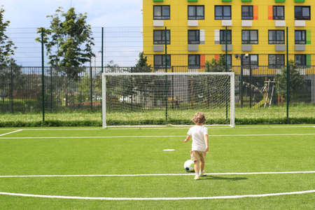 little boy in a white t-shirt playing football