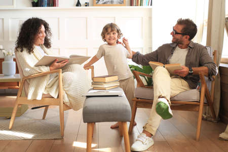 Young family with a cute little son reading books together at home Standard-Bild
