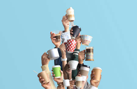 People are holding mugs and paper cups of coffee. Concept on the theme of cafes and coffee. Christmas tree.