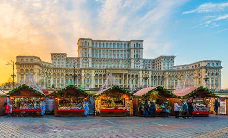 Christmas market and decorations in center of Bucharest, Parliament building in background, Romania