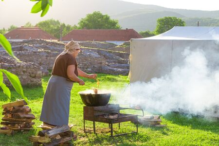 Woman cooking romanian traditional food on fire outdoor in a camping holiday in summer season Stock Photo