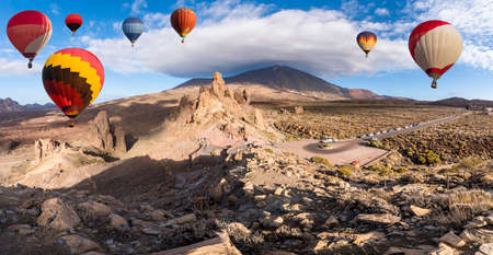 Landscape with hot air balloons flying in Teide National Park, Tenerife, Canary Islands, Spain. In background Roques de Garcia stone and Teide mountain volcano