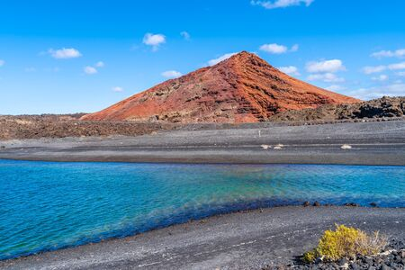 Landscape with red volcano near Los Hervideros caves in Lanzarote, Canary Islands, Spain
