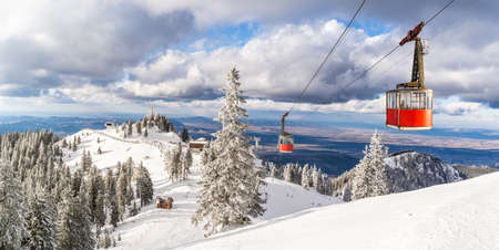 Landscape from top of Postavaru mountain with ski slopes and cable car transporting in Poiana Brasov, Romania