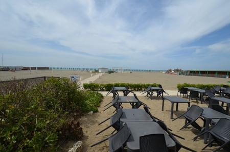 Patio, terrace is golfcart, golf cart and folding chair. That marvel has sandbar, sand bar and that beauty contains seashore, coast, seacoast, sea-coast. Stock Photo