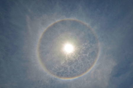 Full circle rainbow around Sun at noon, rays catch the thin vapour formed of ice crystals