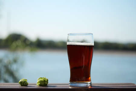 Beer in a glass on the background of the river