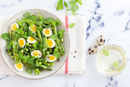 summer salad with quail eggs and asparagus on the table