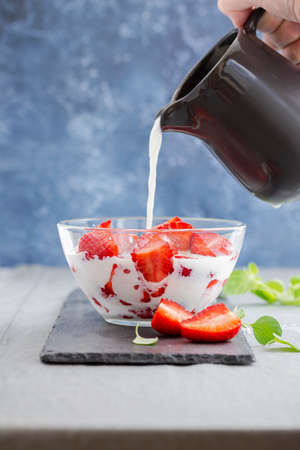 a stream of milk pours on strawberries Stockfoto