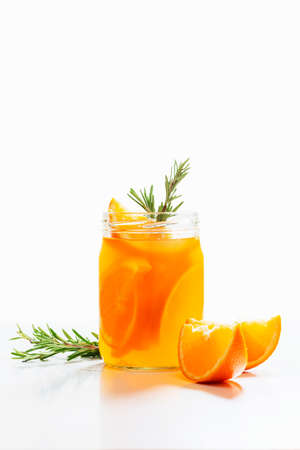 Christmas punch with oranges, rosemary and cranberries on a white background