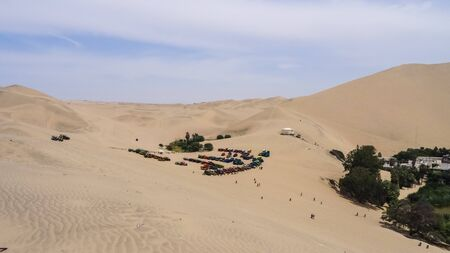 Sandboarding in oasis Huacachina. Miracle of Peru, a lot of sands and a beautiful small lake. Unusual hobby Фото со стока - 130810342