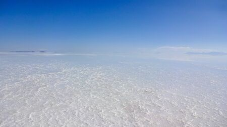 Panoramic photo of bolivian Salar de Uyuni, amazing place in South America. Surface with water makes a mirror.