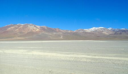 Amazing mountains and volcanos, flamingos and lamas on Altiplano tableland in Bolivia, South America.