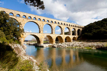 Pont du Gard. Blue sky. Reflection in water. Stock Photo