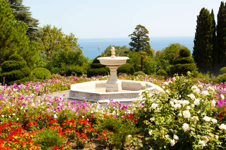 Marble Fountain in the park among flowers Stock Photo