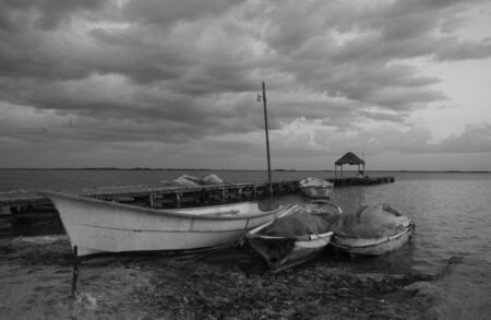 beach and ocean pier panorama with fisher boat in chelem mexico photo