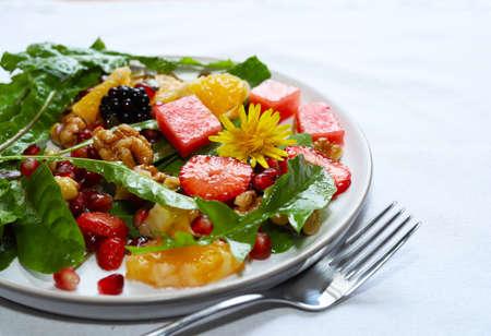 Colorful dandelion salad with fresh fruit.