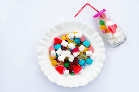 Colorful candys on a white plate. Unhealthy food and too much sugar concept. Stock fotó