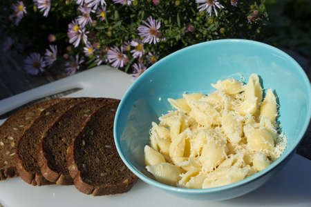 Pasta with cheese and bread on the wooden table in blue bowl photo