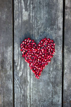 pomegranate seeds in heart shape on grey wooden background photo