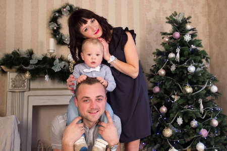 hearthside: Happy family sitting in front of fireplace at christmas holiday