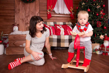 Mother playing with her child in christmas decoration in front of christmas-tree photo