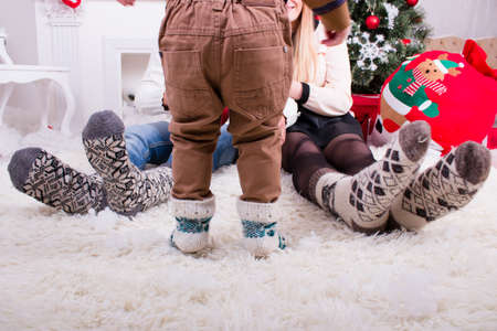 cosy: feeds of man woman and they child in knitted socks near christmas tree Stock Photo