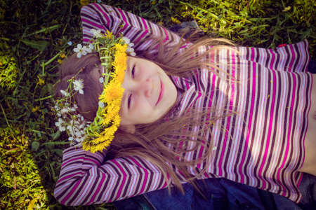 chaplet: Little girl with chaplet on head sitting on a grass in the garden